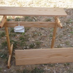 This table has a simple two plank top. There are pegs that keep the top from sliding.
